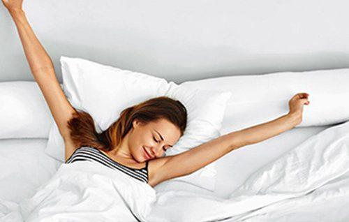 Ein Frau wacht auf und streckt sich