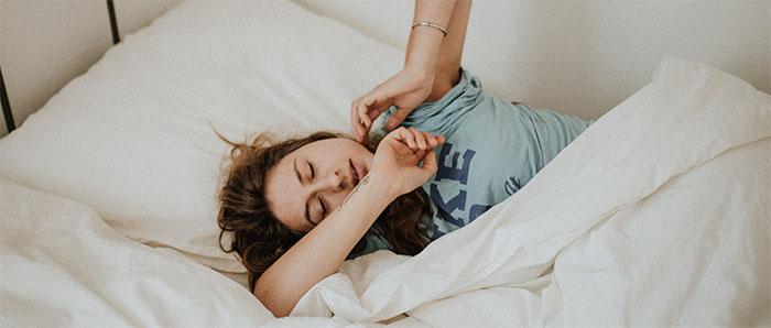 Schöne Frau auf der Suche nach der optimalen Schlafzimmertemperatur